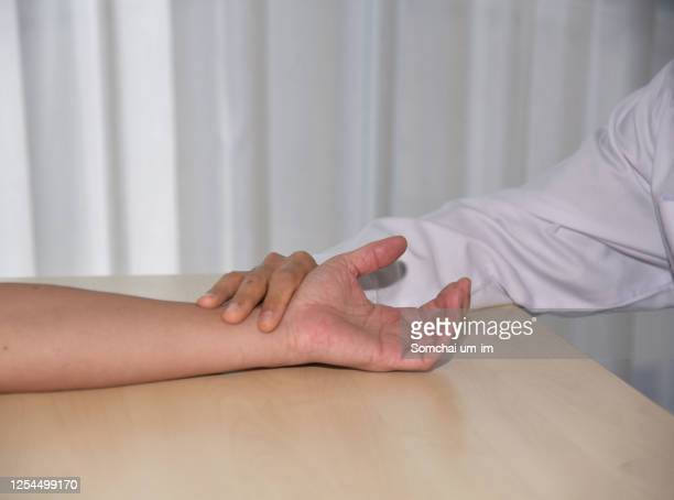 asian male doctor checking patient 's pulse and holding patient 's hand for encouragement - cardiovascular system stock pictures, royalty-free photos & images