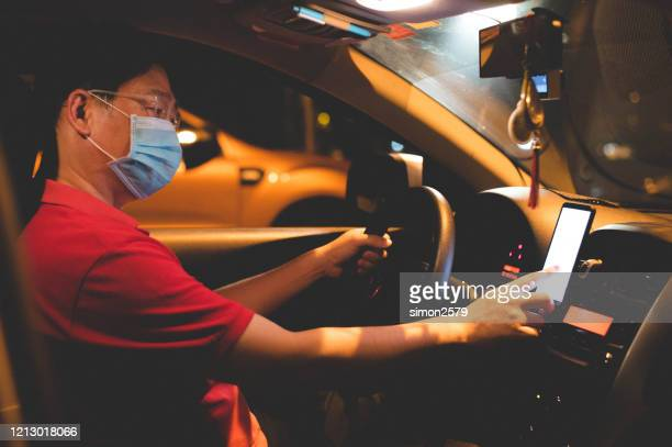 asian male e-hailing driver with face mask using smartphone - driving stock pictures, royalty-free photos & images