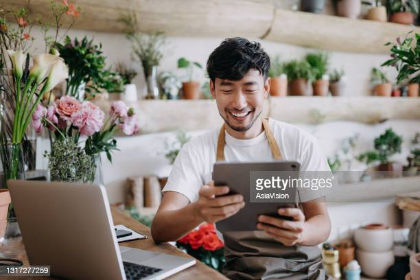 asian male florist, owner of small business flower shop, using digital tablet while working on laptop against flowers and plants. checking stocks, taking customer orders, selling products online. daily routine of running a small business with technology - owner stock pictures, royalty-free photos & images