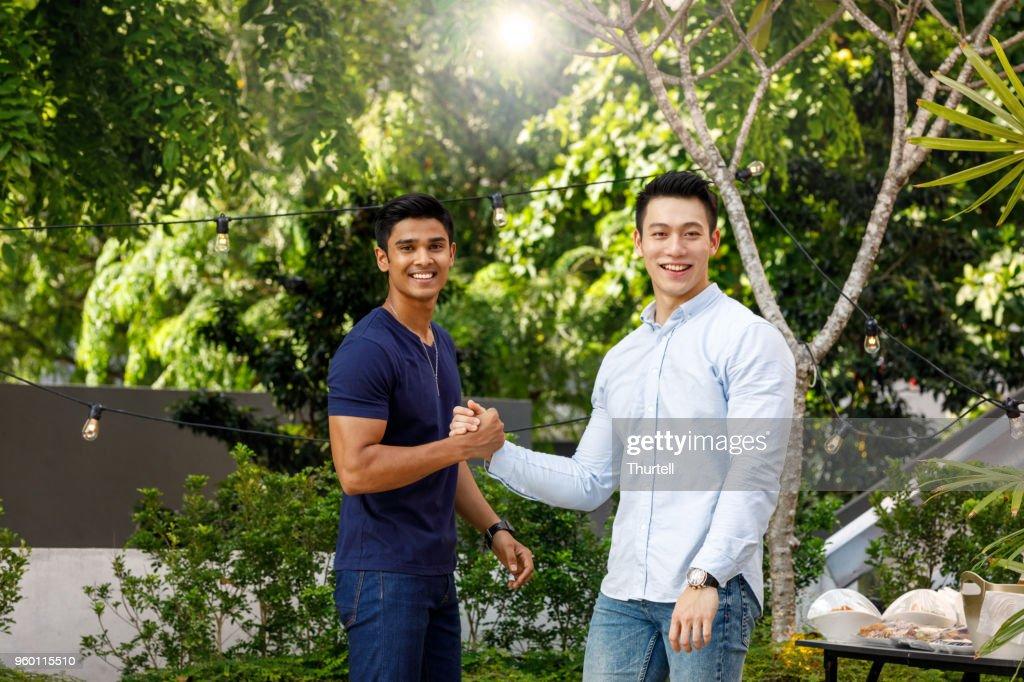 Asiatischen männlichen Freunde Gruß einander am Dach Top Party im freien : Stock-Foto