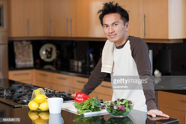 Asian Male in Kitchen Making Salad