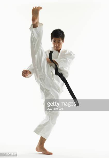 asian male karate black belt kicking in air - martial arts stock photos and pictures