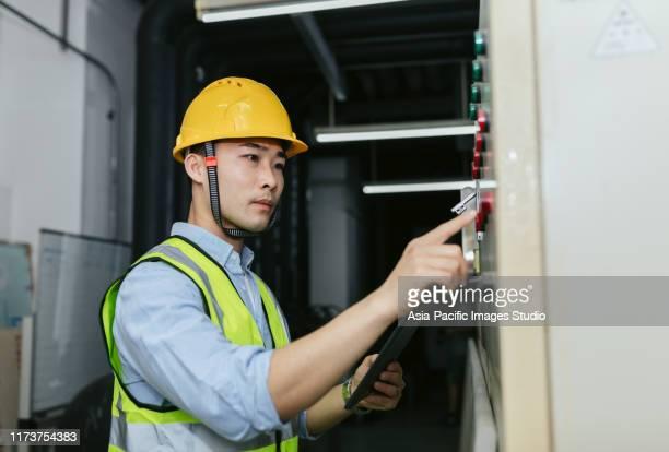 エネルギー制御室で働くアジアの男性メンテナンスエンジニア。エンジニアリングとビジネスの概念。 - 電気 ストックフォトと画像