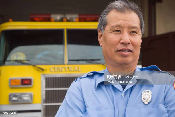Asian male paramedic in front of ambulance