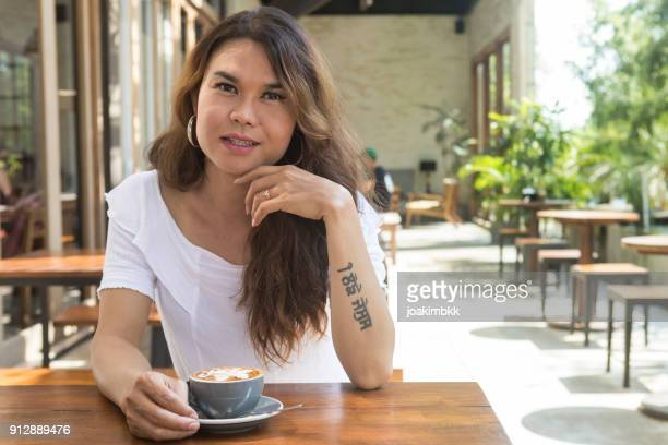 asian male transgender portrait with cappuccino in outdoor restaurant - transgender woman stock photos and pictures