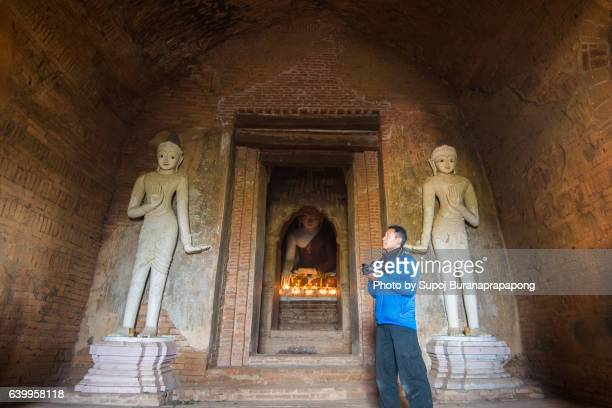 Asian male traveler photographing in the temple at Bagan Myanmar