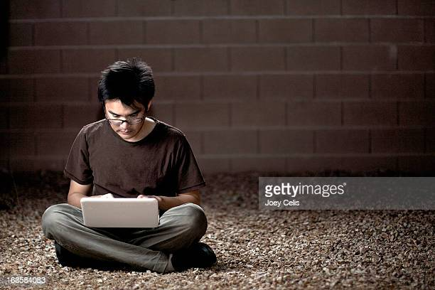 asian male using a wireless notebook outside - 胡坐 ストックフォトと画像