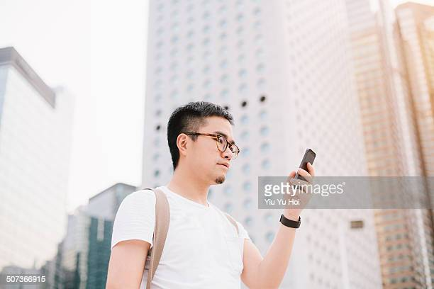 Asian male using smartphone in modern city