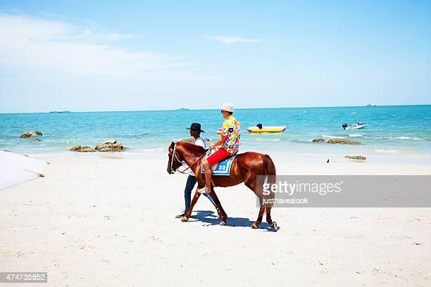 Homme asiatique et touristique cheval d'équitation sur la plage de Hua Hin