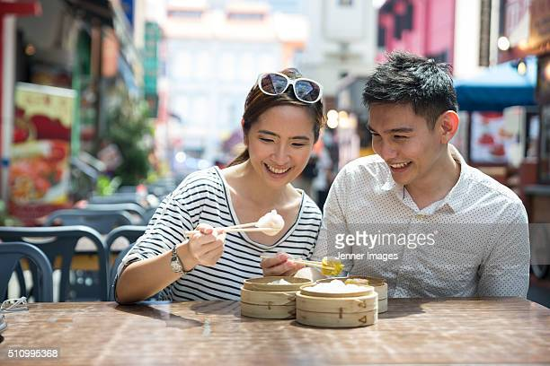 Asian man and woman eating dumplings.