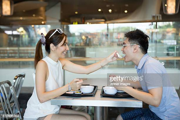 Asian man and woman out for lunch in a food court.