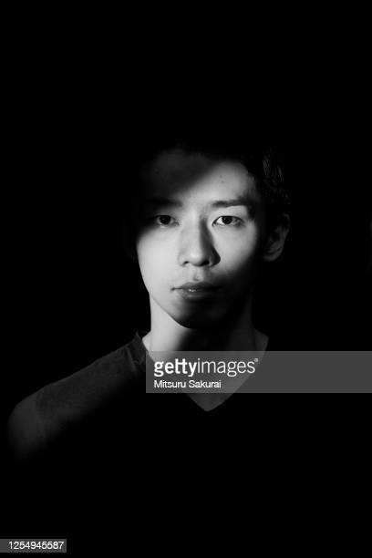 asian man and woman with side spotlight against black background. - vertical stock pictures, royalty-free photos & images