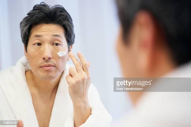 Asian man applying face cream
