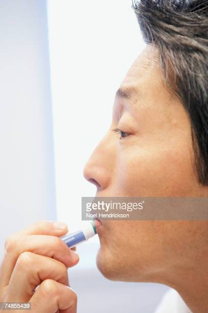 asian man applying lip balm - dry mouth stock photos and pictures