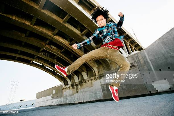 Asian man break dancing under overpass