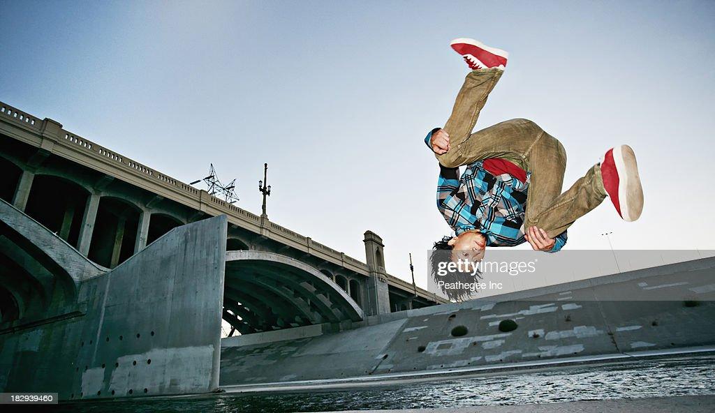 Asian man break dancing under overpass : Stock Photo