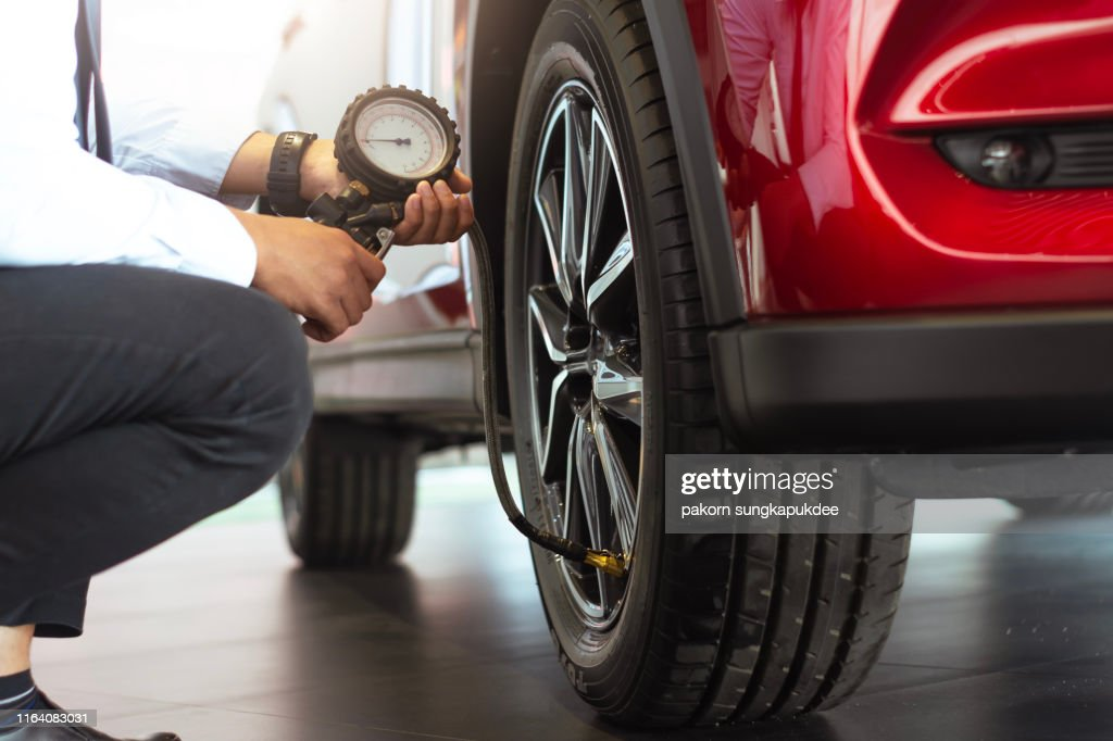 Asian man car inspection Measure quantity Inflated Rubber tires car.Close up hand holding machine Inflated pressure gauge for car tyre pressure measurement for automotive, automobile image : Stock Photo
