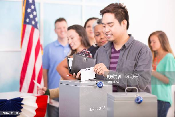 Asian man casts ballot. November USA election. Voters background.