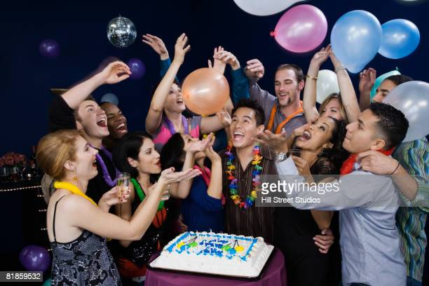 Asian man celebrating birthday with friends