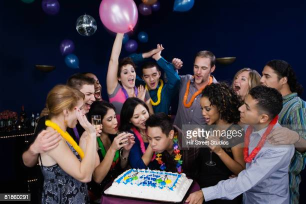asian man celebrating birthday with friends - birthday cake lots of candles stock photos and pictures