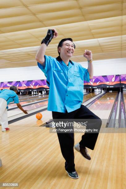 Asian man cheering in bowling alley