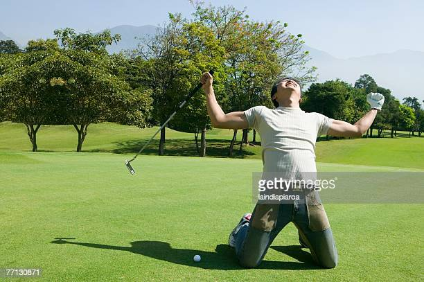 Asian man cheering on golf course