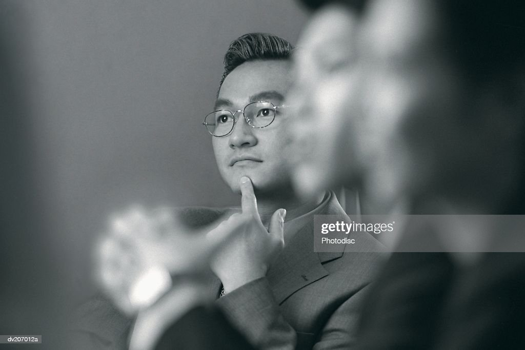 Asian man concentrating during meeting : Stock Photo
