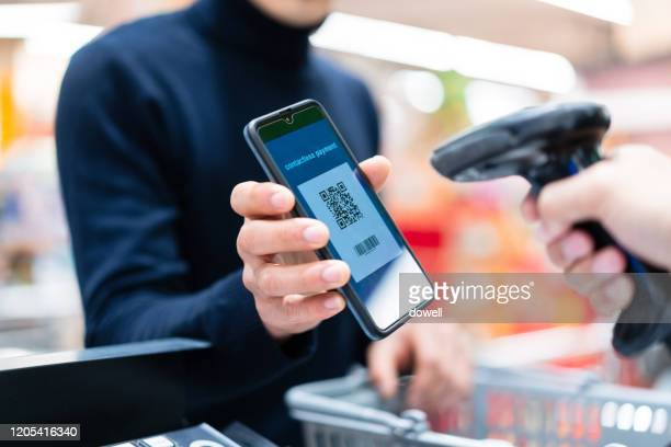 asian man contactless payment with qr code in supermarket - financial technology stock pictures, royalty-free photos & images
