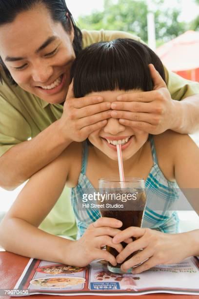 Asian man covering girlfriend's eyes
