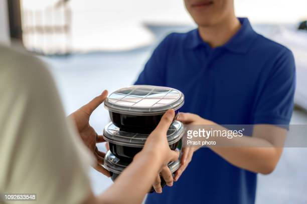 asian man delivering food in black boxes to customer home. - box container stock pictures, royalty-free photos & images