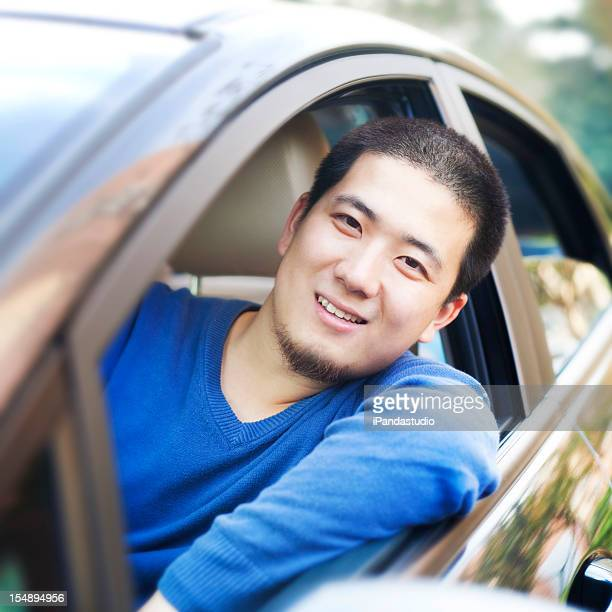 Asian man driving car
