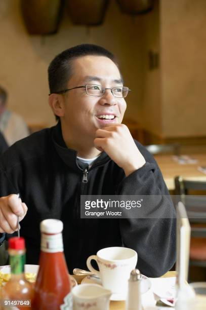 Asian man eating in restaurant