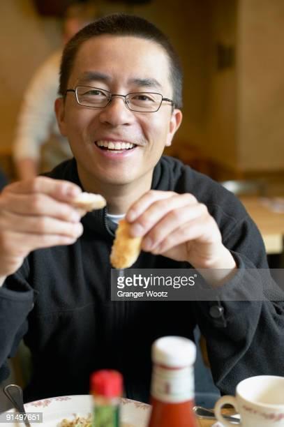 Asian man eating in restaurant