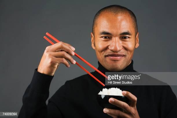 Asian man eating rice with chopsticks