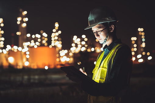 Asian man engineer using digital tablet working late night shift at petroleum oil refinery in industrial estate. Chemical engineering, fuel and power generation, petrochemical factory industry concept 1156226021