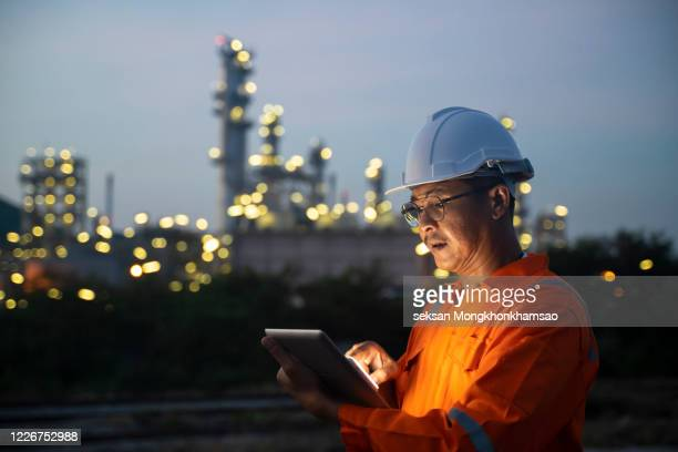 asian man engineer using digital tablet working late night shift at petroleum oil refinery in industrial estate. chemical engineering, fuel and power generation, petrochemical factory industry concept - japan stock pictures, royalty-free photos & images