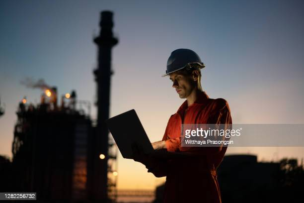 asian man engineer using digital tablet working late night shift at petroleum oil refinery - factory stock pictures, royalty-free photos & images