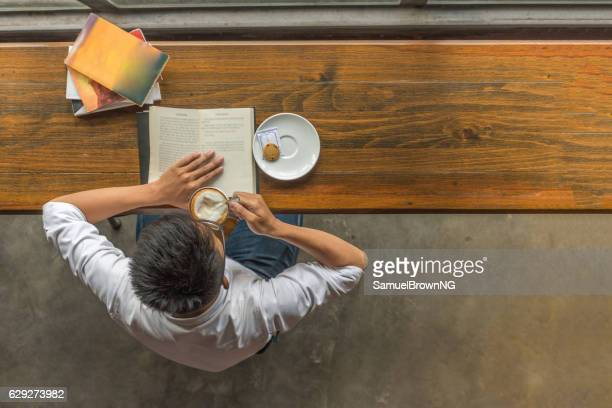 Asian man enjoying a beautiful day with book and coffee