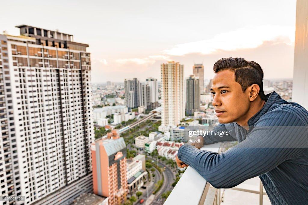 Asian Man Enjoying The Sunset View Over Bangkok : Stock Photo