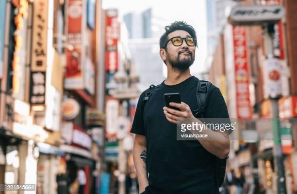 homem asiático explorando a cidade, segurando um smartphone na mão - só homens de idade mediana - fotografias e filmes do acervo