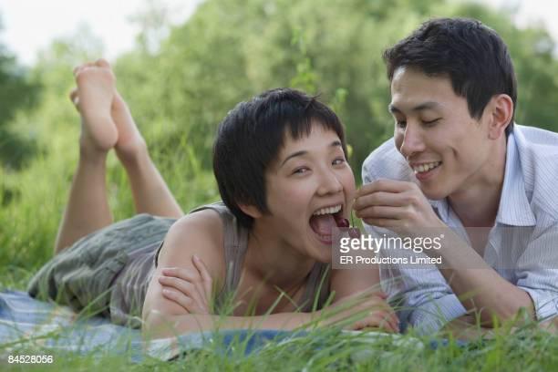 Asian man feeding girlfriend cherries