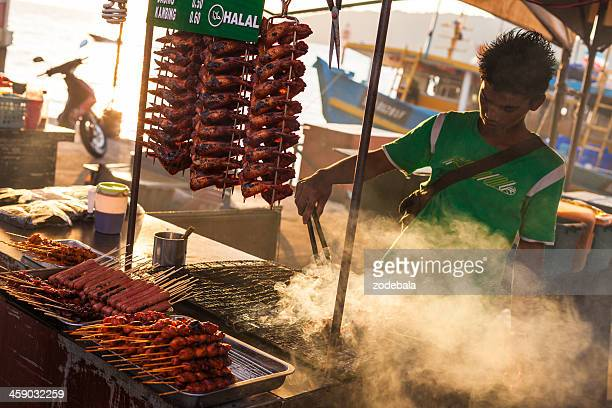 asian man grilling chicken on a food stall, malaysia - gerookte worst stockfoto's en -beelden