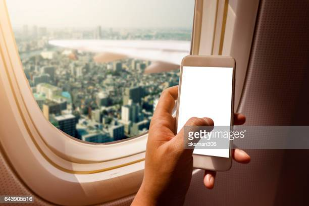 Asian man hand holding i phone 6  on board of airplane near window seat and wing