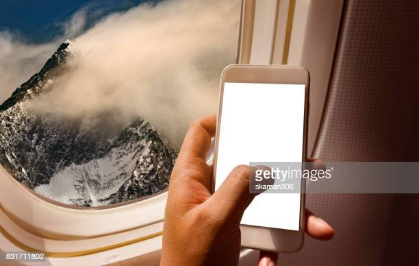 Asian man hand holding smart-phone start up working  on board of airplane near window seat and wing with alps mountain
