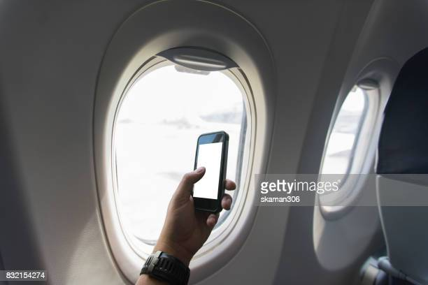 Asian man holding a smart-phone on an airplane