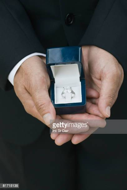 asian man holding engagement ring - man holding engagement ring stock photos and pictures