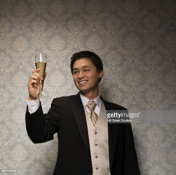 Asian man holding glass of champagne