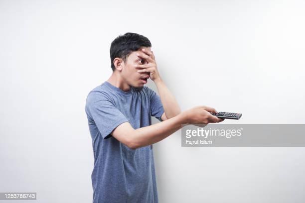 asian man holding remote tv - controllato a distanza foto e immagini stock