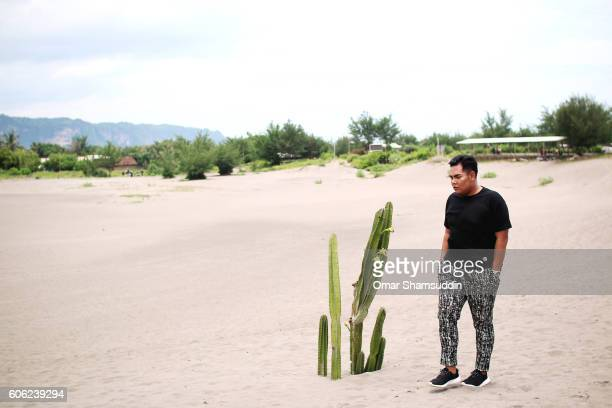 asian man in black tshirt at sand dune in yogyakarta - omar shamsuddin stock pictures, royalty-free photos & images
