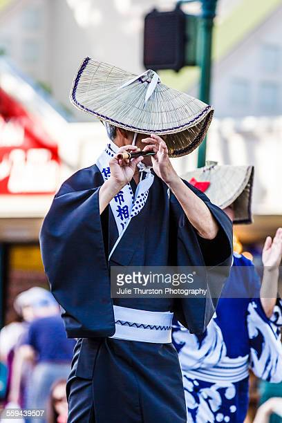 Asian man in colorful traditional costume and headwear marching and playing the flute bamboo reed in the annual downtown Pan Pacific Parade in...
